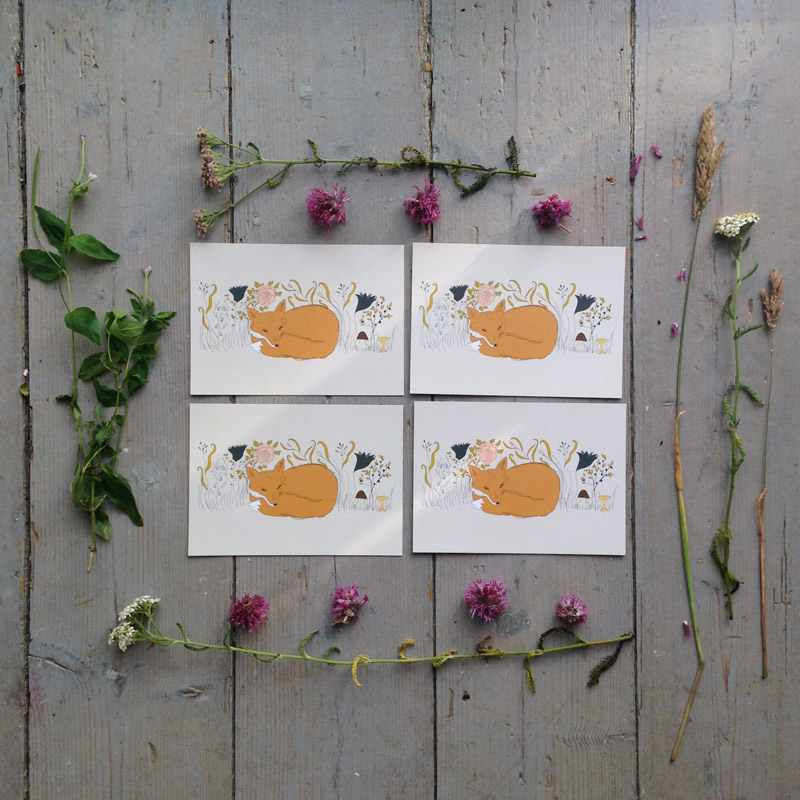 Four fox cards on a grey cottage floor with flowers around them